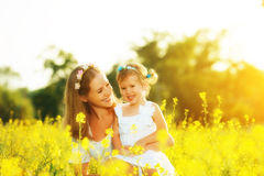 Happy family in summer meadow, mother embrace little daughter ch Royalty Free Stock Photography