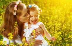 Happy family in summer meadow, mother kissing little daughter ch. Happy family in the summer meadow, mother kissing little daughter girl child with yellow Royalty Free Stock Images