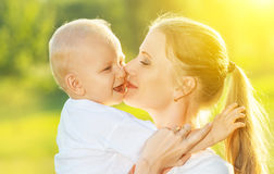 Happy family in summer. mother kissing her baby royalty free stock photo
