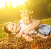 Happy family in summer nature. Mother and baby daughter on hay Stock Photos