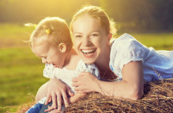 Happy family in summer nature. Mother and baby daughter in the hay, straw Stock Photography