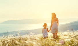 Happy family in summer outdoors. Mother and child daughter stand Stock Photos