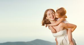 Happy family in summer outdoors.   mother  hug child daughter an. Happy family in the summer outdoors.   mother hug child daughter and laughing Royalty Free Stock Image