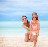 Happy family during summer vacation on white beach. Beautiful mother and her adorable little daughter at beach Royalty Free Stock Photos