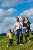 Happy family in summer on a walk. Happy family (father, mother and two sons) having a walk on a beautiful summer day stock image