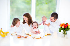 Happy family on Sunday morning having breakfast. Happy young family with a teenage boy, adorable curly toddler girl and a newborn baby having fun together on a Stock Image