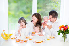 Happy family on Sunday morning having breakfast. Happy young family with a teenage boy, cute curly toddler girl and a newborn baby having fun together on a Stock Photo