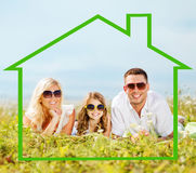 Happy family in sunglasses outdoors. Home, happiness and real estate concept - happy family in sunglasses lying on a grass with house shaped illustration Royalty Free Stock Photography