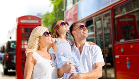 Happy family in sunglasses over london city street. Summer holidays, travel, tourism and people concept - happy family in sunglasses looking up over london city Stock Photos