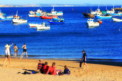 Happy Family on Sunny Beach with Blue Waters and Boat. A happy family sits on the beach in Cascais, Portugal near Lisbon. Children run into the ocean. Boats sit Royalty Free Stock Image