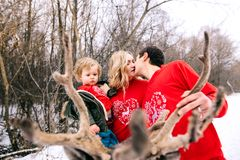 Happy family at sunset. Father, mother and child daughters are having fun and playing on snowy winter walk in nature, kiss. Frost royalty free stock images