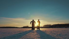 Happy family at sunset. Father, mother and little son are having fun and playing on snowy winter walk in nature.