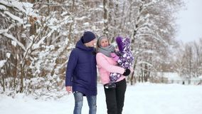 Happy family at sunset. Father, mother and two children daughters are having fun and playing on snowy winter walk in stock video footage
