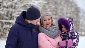 Happy family at sunset. Father, mother and two children daughters are having fun and playing on snowy winter walk in stock video