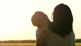 Happy family at sunset. The mother holds the child in her arms, hugging him. A little boy experiences emotions of love