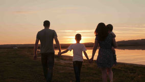Happy family on sunset silhouette Stock Photos