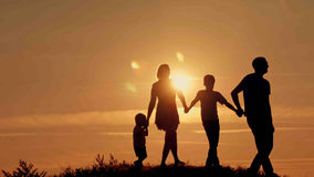 Happy family on sunset silhouette Stock Photo