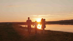 Happy family on sunset silhouette Stock Image