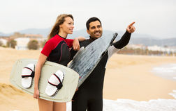 Happy family with surf boards. Happy family on the shore in wetsuits with surf boards stock photography