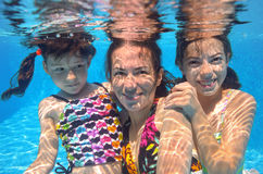 Happy family swim underwater in pool Stock Photos