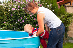 Happy family and swimming pool. Young women and toddler discovering swimming pool in the garden Stock Photos