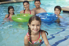 Happy Family In Swimming Pool. Portrait of a cute elementary girl in swimming pool with family in the background Stock Photo