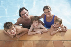 Happy Family In Swimming Pool. Elevated portrait of a happy couple with three children in swimming pool Royalty Free Stock Image