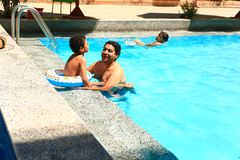Family at swimming pool. Happy family swimming at pool Stock Photography