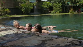 Happy family in the swimming pool. Mother and her two daughters in a swimming pool with mineral water springs.Family Outside Relaxing In Swimming Pool.Pool, fun stock video