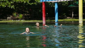 Happy family in the swimming pool. Mother and her two daughters in a swimming pool with mineral water springs.Family Outside Relaxing In Swimming Pool.Travel stock video footage