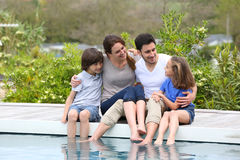 Happy family by swimming pool Stock Photos