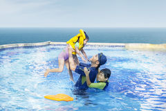 Happy family swimming on the pool. Happy family playing on the swimming pool together Royalty Free Stock Photography