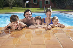 Happy Family In Swimming Pool. Portrait of a happy couple with three children in swimming pool stock images