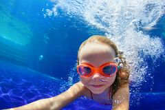Funny child in goggles dive in swimming pool royalty free stock image