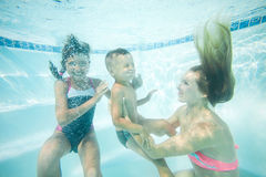 Happy family swimming underwater. Mother, son and daughter having having fun in pool. Stock Photos
