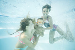 Happy family swimming underwater. Mother, son and daughter having having fun in pool. Royalty Free Stock Images