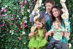 Happy family on swing look toward near hedge stock photo
