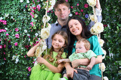 Happy family on swing near hedge with flowers Stock Photos