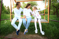 Happy family on the swings in the garden on Sunday. Happy family pregnant mom,happy father and little daughter on the swing in the garden on Sunday Royalty Free Stock Image