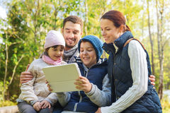 Happy family with tablet pc at camp. Camping, travel, tourism, hike and people concept - happy family with tablet pc computer at camp in woods Stock Photo