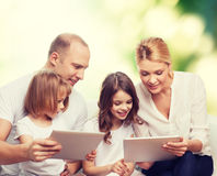 Happy family with tablet pc computers. Family, ecology, technology and people - smiling mother, father and little girls with tablet pc computers over green Royalty Free Stock Photos
