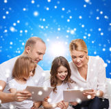Happy family with tablet pc computers. Family, holidays, christmas technology and people - smiling mother, father and little girls with tablet pc computers over Royalty Free Stock Photo