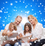 Happy family with tablet pc computers. Family, holidays, christmas technology and people - smiling mother, father and little girls with tablet pc computers over Royalty Free Stock Image