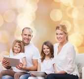 Happy family with tablet pc computers. Family, holidays, technology and people - smiling mother, father and little girls with tablet pc computers over beige Stock Images