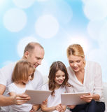 Happy family with tablet pc computers. Family, holidays, technology and people - smiling mother, father and little girls with tablet pc computers over blue Royalty Free Stock Images