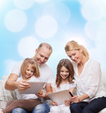 Happy family with tablet pc computers. Family, holidays, technology and people - smiling mother, father and little girls with tablet pc computers over blue Royalty Free Stock Photos