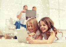 Happy family with tablet pc computers. Family, home, technology and people - smiling mother, father and little girls with tablet pc computer over snowflakes Royalty Free Stock Image
