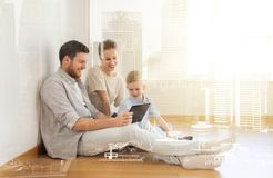 Happy family with tablet pc moving to new home Stock Images