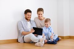 Happy family with tablet pc moving to new home Stock Photo