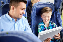 Happy family with tablet pc sitting in travel bus Royalty Free Stock Image
